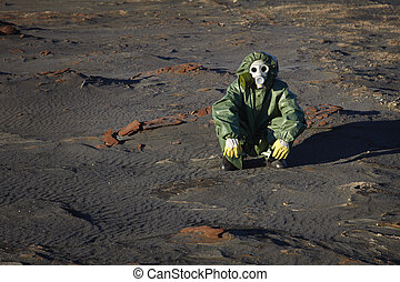 Man in protective clothing sitting in desert - A man in...
