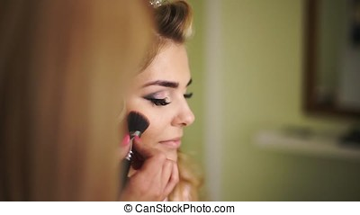 Beautiful woman face powders, and apply blush to the...