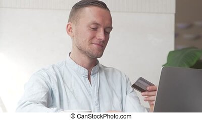Man using computer for online purchase with credit card -...