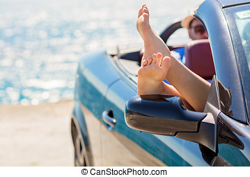 Girl having fun in blue cabriolet against toned sky background. Summer vacation and travel concept