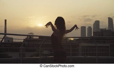 Young woman dancing on the roof on sunset. Urban background