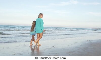 Mother with daughter walking on seashore.