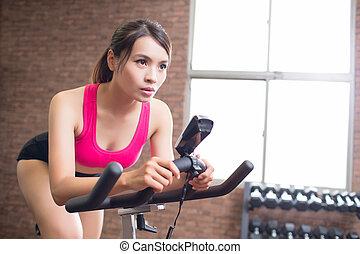 woman use exercise bike and training hard