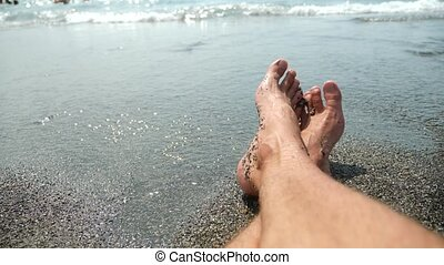 Foot men on the beach next to the surf line, sea view. 4k....
