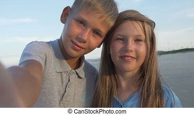 Closeup of blonde little brother and sister taking selfie together