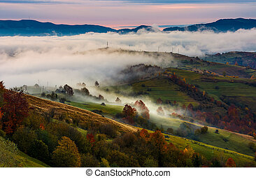 rising fog covers rural fields in mountains. spectacular...