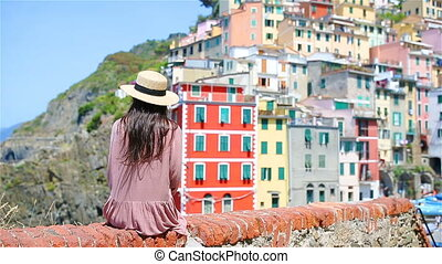 Young woman with great view at old village Riomaggiore,...