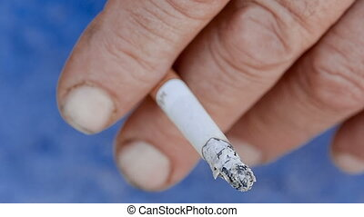Hand with a burning cigarette.