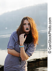 young woman with black lipstick - young woman standing in...