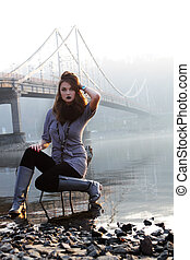 young woman siting on the chair in the water and fog
