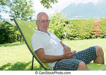 Senior man relaxing in the deckchair in his garden, summer...