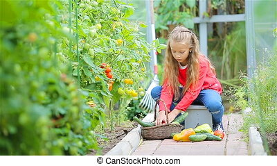 Adorable little girl in greenhouse in summer day - Cute...