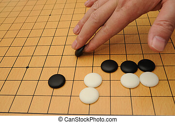 Playing go game - A hand putting go stone to the board
