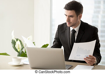 Serious businessman holding financial report, analyzing project