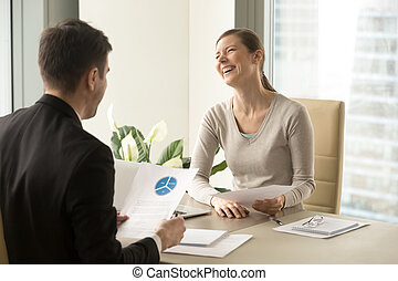 Happy positive colleagues laughing during meeting, having...