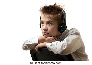 Young boy listening to head phones isolated on white