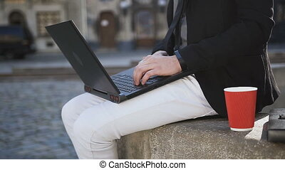 A young business man in glasses work on a computer in the city and drinks coffee