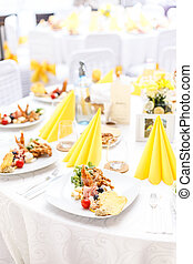 Table appointment for guests with appetizers on a banquet...