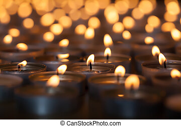 Lighted candle amongst many flaming tea light candles....