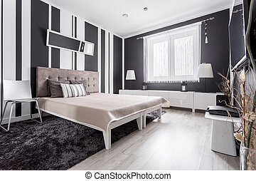Luxurious modern bedroom with striped wallpaper and bed with...