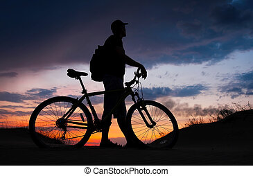 Silhouette of cyclist on the background of sunset. Biker...