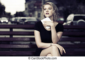 Young fashion woman with tablet computer sitting on a bench