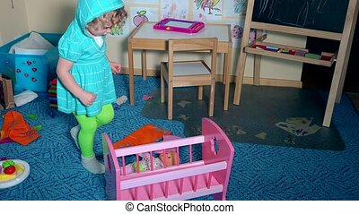 Sweet little toddler girl lay down baby doll into toy bed...