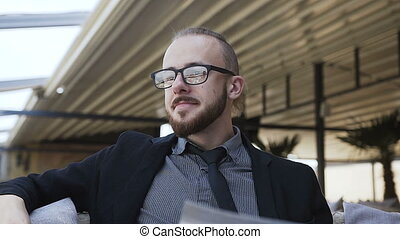 A young man with a beard in glasses is happy at work