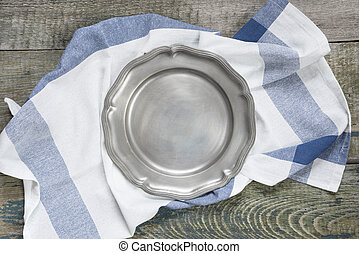 Pewter plate on a rough wooden table - Empty pewter plate...