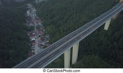 Aerial shot of a highway bridge and a tunnel in mountains in...