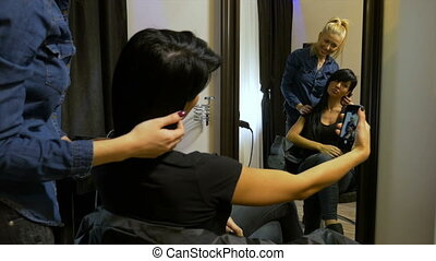 Young attractive woman taking selfie with her hairdresser at...