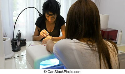 Beautician performs semi permanent manicure and invites...