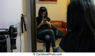 Young girl sitting on chair and texting on mobile phone at...