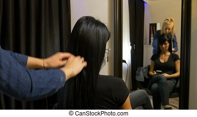 Hairdresser getting beautiful woman prepped for event
