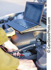 Mechanic using electricity meter - Mechanic measuring engine...