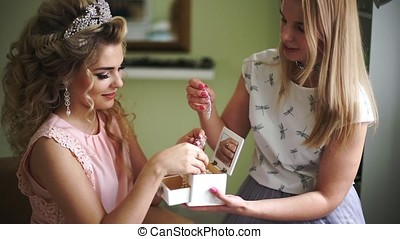 Bride with make-up artist chooses beautiful ornaments from...