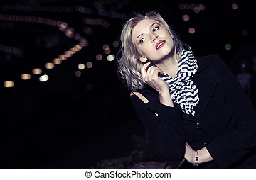 Young blond fashion woman on the night city street