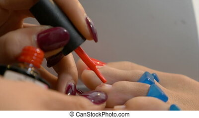 Woman gets professional pedicure with elegant red nail...