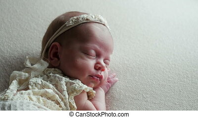 beautiful sweet baby girl in a suit sleeping in the crib