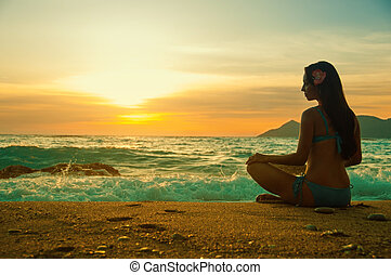 Silhouette woman yoga on the sea beach at sunset