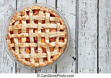 Homemade peach pie, above view on white wood - Rustic...