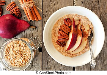 Oatmeal with red pear, pecans and cinnamon, overhead scene...