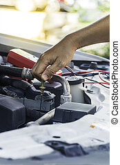 Auto mechanic uses hand of technician checking or fixing engine of in a car.