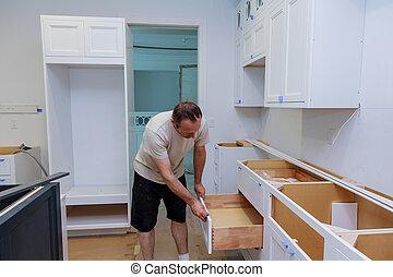 Installation kitchen. Worker installs doors to kitchen cabinet.