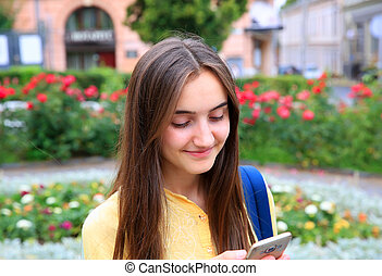 Beautiful girl with mobile phone reads a message in the...