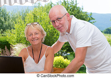 Senior couple using laptop computer at home - a senior...