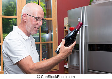 mature man with bottle of red wine, on the kitchen - a...