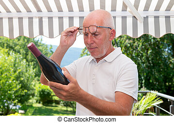 mature man with bottle of red wine, on the terrace - mature...