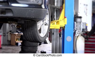 car lowering on lift in auto repair garage service.
