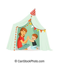 Mum and her son playing in a tepee tent, kid having fun in a...